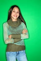 Portrait of smiling Asian_American teen girl with arms crossed standing in front of green background