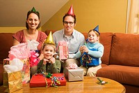 Caucasian family celebrating a birthday party and looking at viewer