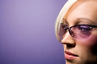 Close_up portrait of young adult Caucasian blond woman on purple background wearing sunglasses