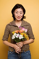 Asian woman holding bouquet of flowers