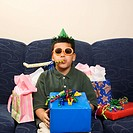 Hispanic boy with birthday party favors and presents looking at viewer (thumbnail)