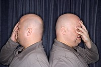 Profile of Caucasian bald identical twin men standing back to back and grimicing with hands to head