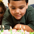 Hispanic boy looking down wishfully at lit candles of birthday cake with girl peeking in over his shoulder