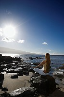 Young adult Asian Filipino female meditating on rocky beach (thumbnail)