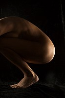 Side view of nude Hispanic mid adult woman crouching with knees to chest