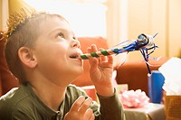 Caucasian boy at birthday party blowing noisemaker (thumbnail)