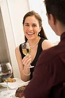 Mid adult Caucasian couple smiling and drinking wine and dining