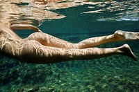 Caucasian young nude female body swimming underwater
