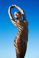 Filipino young nude woman with arms stretched overhead standing with sun streaks over body