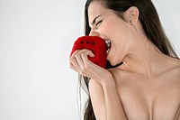 Topless Caucasian woman biting fuzzy dice