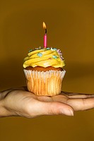 Caucasian prime adult female hand holding cupcake with lit candle