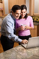MId_adult couple looking at laptop computer while drinking coffee in kitchen