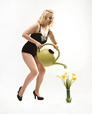 Attractive Caucasian woman wearing retro swimsuit in pinup pose watering flowers