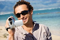 Mid-adult Caucasian man on beach pointing video camera at viewer (thumbnail)