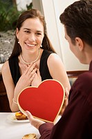 Mid adult Caucasian man giving a heart shaped box of chocolates to woman at restaurant
