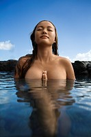 Young Asian nude woman partially submerged in water with eyes closed and hands together