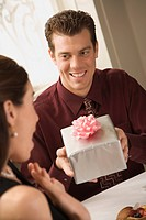 Mid adult Caucasian man presenting wrapped gift to surprised woman at restaurant