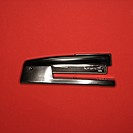 Black stapler on red background