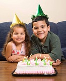 Hispanic girl and boy wearing party hats sitting in front of birthday cake smiling and looking at viewer