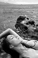 Topless Caucasian mid adult woman on rocky coast lying on back with eyes closed