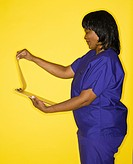 African_American mid_adult woman n medical uniform smiling reading chart