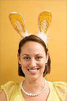 Caucasian mid adult woman wearing rabbit ears and looking at viewer