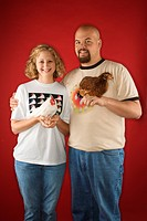 Caucasian mid_adult man and woman holding chickens