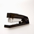 Black stapler on white background