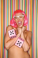 Portrait of attractive Caucasian young adult woman wearing pink wig against striped background holding large pink dice and making sassy expression