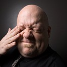 Caucasian mid adult bald man rubbing eye and making facial expression