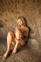 Young nude female sitting in a cave