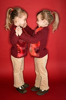 Female children Caucasian twins standing in dance stance