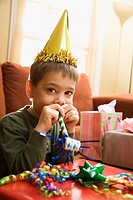Caucasian boy at birthday party looking at viewer blowing noisemaker