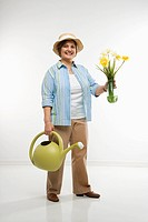 Caucasian middle aged woman holding flowers and watering can