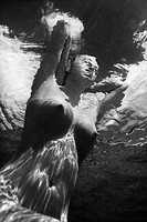Underwater view of young Asian nude woman partially submerged sitting with hands behind head