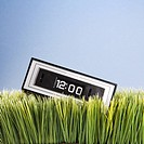 Studio shot of retro alarm clock placed in grass