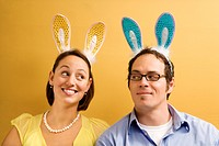 Caucasian mid adult couple wearing rabbit ears and looking at each other