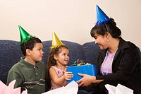 Mother giving present to daughter at birthday party (thumbnail)
