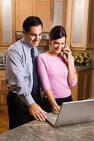 MId_adult female talking on phone and mid_adult male both looking at laptop computer in kitchen