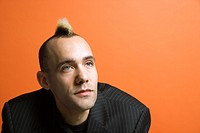 Caucasian man in suit with mohawk against orange background