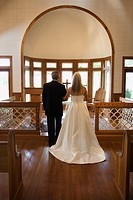 Portrait of bride and groom at alter of a church