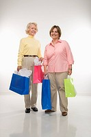 Caucasian senior woman and middle aged woman holding gift bags smiling at viewer