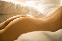 Nude Caucasian mid_adult female back and buttocks surrounded by pillows
