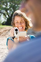 Mid_adult Caucasian woman outdoors pointing video camera at man