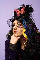 Portrait of Caucasian woman in unique makeup and clothing against purple background