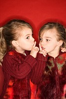 Female children Caucasian twins with fingers up to lips