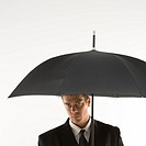 Caucasian mid_adult businessman looking out at viewer from under umbrella