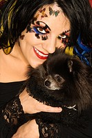Smiling Caucasian woman in unique makeup holding black Pomeranian dog