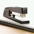 Black stapler on top of a spiral bound notebook