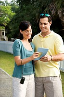Mid_adult Caucasian couple holding map and smiling